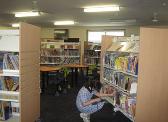 Student reaching for book inside library